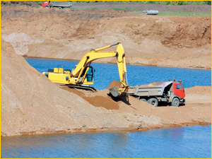 Экскаватор добывает речной песок и загружает в самосвал