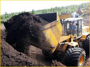Погрузчик сортирует грунт и землю для погрузки
